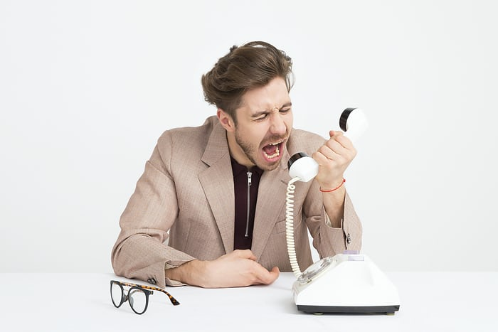 Frustrated remote employee taking out anger on phone